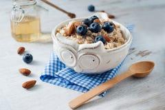 Светлый завтрак овсяной каши с миндалиной и голубикой Стоковые Изображения