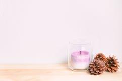 Свеча в стеклянном опарнике и 3 конуса сосны на деревянном столе Стоковые Фото