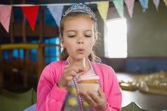 Свеча девушки дня рождения дуя на пирожном Стоковое фото RF
