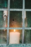Свеча за пакостным окном Стоковые Изображения