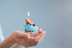 Свеча именниного пирога одиночная в руках над голубой предпосылкой Holid Стоковые Фотографии RF