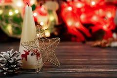 Свеча и игрушки рождества на предпосылке гирлянды освещают на bla Стоковое Фото