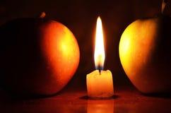 Свеча между яблоками Стоковая Фотография