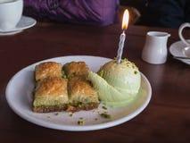 Свеча дня рождения в ветроуловителе мороженого и bakalava Стоковые Изображения