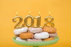 2018 свечей горя на штабелированном Новом Годе donuts счастливом Стоковые Фото