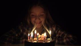 Свечи в ночи, ребенк дня рождения ребенка дуя празднуют с тортом в темноте акции видеоматериалы