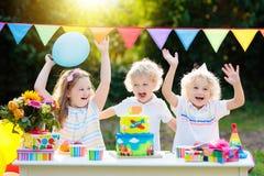Свечи дуновения детей на именнином пироге Партия детей стоковые фото