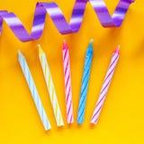 Свечи и лента на желтой предпосылке Подготавливать для дня рождения Стоковое фото RF