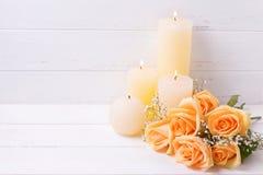 Свечи и персик красят цветки роз на белом деревянном backgroun Стоковые Фотографии RF