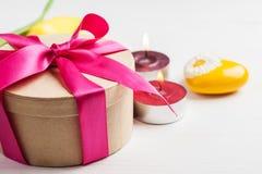 Свечи и подарочная коробка Lit с красной лентой Стоковые Изображения RF