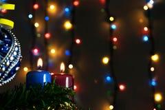 2 свечи и рождества забавляются с пестроткаными светами на предпосылке Стоковое фото RF