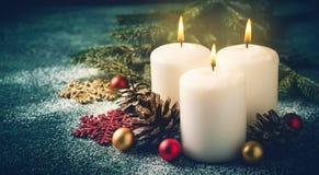 3 свечи и украшения рождества горящих на темной предпосылке бирюзы Стоковое Изображение