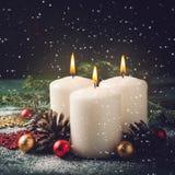 3 свечи и украшения рождества горящих на темной предпосылке Стоковое Изображение