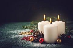 3 свечи и украшения рождества горящих на темной предпосылке Стоковые Фотографии RF