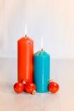 2 свечи и 3 шарика рождества на деревянной поверхности стоковое фото