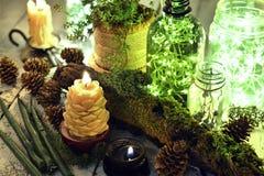 Свечи свечи конуса, зеленых и черных с освещать бутылки на деревянном столе стоковое изображение