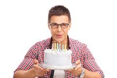 Свечи радостного человека дуя на именнином пироге Стоковое фото RF