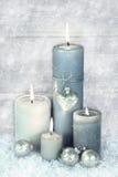 Свечи рождества 4 синь, серого и белых горящие с снегом внутри Стоковые Изображения
