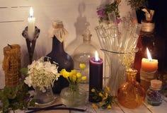 Свечи, стеклянные бутылки, опарникы и цветки на таблице Стоковые Изображения