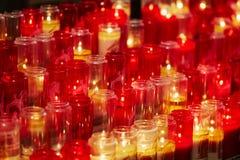 Свечи церков в красных и желтых прозрачных люстрах Стоковая Фотография RF