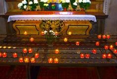 Свечи церков в красных и желтых прозрачных люстрах Стоковые Изображения RF
