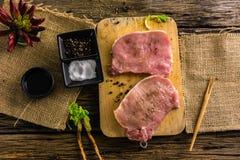 Свинина взгляд сверху сырцовый 2 части имеет специи и перец Масло и соль на старом деревянном столе Стоковая Фотография