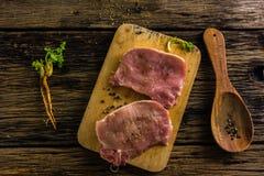 Свинина взгляд сверху сырцовый 2 части имеет специи и перец Масло и соль на старом деревянном столе Стоковые Изображения RF