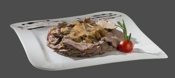 Свинина жаркого с соусом гриба на плите на сером bac Стоковая Фотография