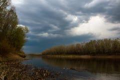 Свинцовые облака собрали над рекой Ural перед заходом солнца стоковое изображение