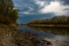 Свинцовые облака собрали над рекой Ural перед заходом солнца стоковые изображения