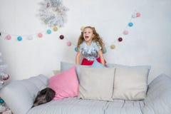 Свинья как символ везения и китайца календарь 2019 Новых Годов Милая смешная девушка удивлена о мини-свинье младенца на софе стоковая фотография