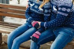 Свитеры и джинсы молодой зимы пар теплые обнимая в парке в зиме сидя на паре деревянной скамьи красивой молодой в влюбленности Стоковое Изображение RF
