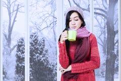 Свитер девушки нося и питье дуновения теплое Стоковое Изображение RF