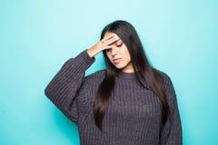 Свитер зимы молодой красивой женщины нося над изолированным голубым страданием предпосылки от усиленной головной боли отчаянной и стоковые фото