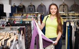 Свитер маленькой девочки покупая в магазине Стоковое фото RF