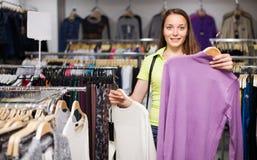 Свитер маленькой девочки покупая в магазине Стоковая Фотография RF
