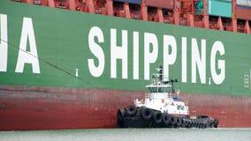 СВОБОДА буксира с левого борта ЗИМЫ грузового корабля CSCL Стоковые Изображения