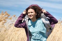 Свобода, концепция душевного спокойствия Красивая молодая женщина идя в золотое пшеничное поле с пасмурной предпосылкой голубого  стоковые изображения rf