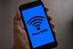 Свободная концепция знака wifi Рука держа мобильный телефон с свободным wifi стоковое фото