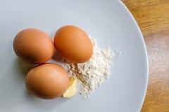 Свободные яичка ряда увиденные с мукой и маслом для делать торт стоковые фото