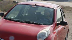Свободный молодой человек управляя автомобилем к обочине, восхищая живописный ландшафт, перемещение сток-видео