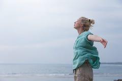 Свободная женщина наслаждаясь ветреной погодой на пляже на день overcast Стоковые Изображения RF