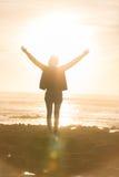 Свободная женщина наслаждаясь свободой на пляже на заходе солнца Стоковое Изображение RF
