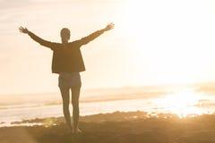 Свободная женщина наслаждаясь свободой на пляже на заходе солнца Стоковое фото RF