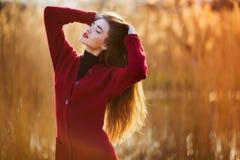 Свободная счастливая молодая женщина Красивая женщина с длинными здоровыми дуя волосами наслаждаясь светом солнца в парке на захо Стоковые Фотографии RF