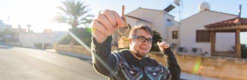Свойство, владение, новый дом и концепция людей Жизнерадостный молодой человек держа ключ дома стоковые изображения rf