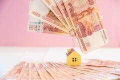 Свойство недвижимости ипотеки нагружая с концепцией банка денег займа деньги и миниатюрная модель дома на пинке стоковое фото