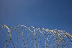 Свяжите проволокой загородку металла сетки круга, острую с бритвами, колючими Ясная предпосылка голубого неба, конец вверх по взг Стоковое фото RF