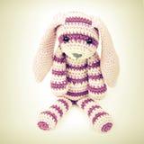 Связанная игрушка кролика сидя над белой предпосылкой Стоковые Изображения