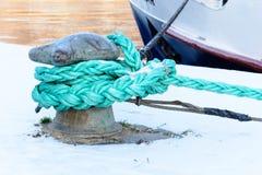 Связанная шлюпка причалила на портовом районе в зиме Стоковое фото RF